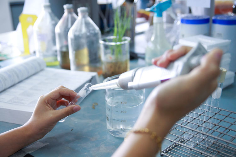 Cropped hands of scientist examining chemical in laboratory