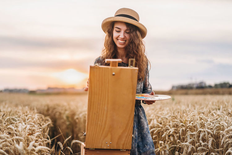 Smiling young woman painting on easel