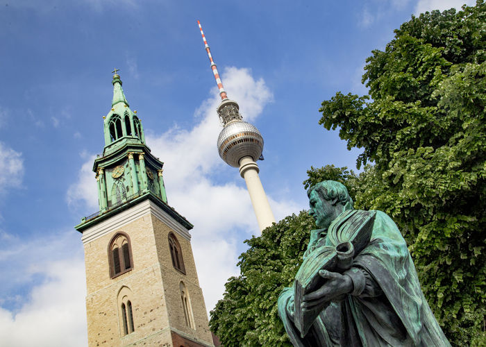 Low Angle View Of Statue And Fernsehturm Against Sky
