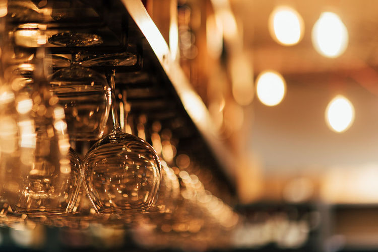 Bar Counter Glass - Material Selective Focus Illuminated Lighting Equipment Indoors  Close-up In A Row No People Focus On Foreground Transparent Upside Down Still Life Arrangement Glass Bar - Drink Establishment Table Shelf Rack Container Wineglass EyeEm EyeEm Selects Bar Bar Counter Restaurants Ambient Light Bokeh Photography Dinner Happy Hour WProductions Hanger Light EyeEm Best Shots