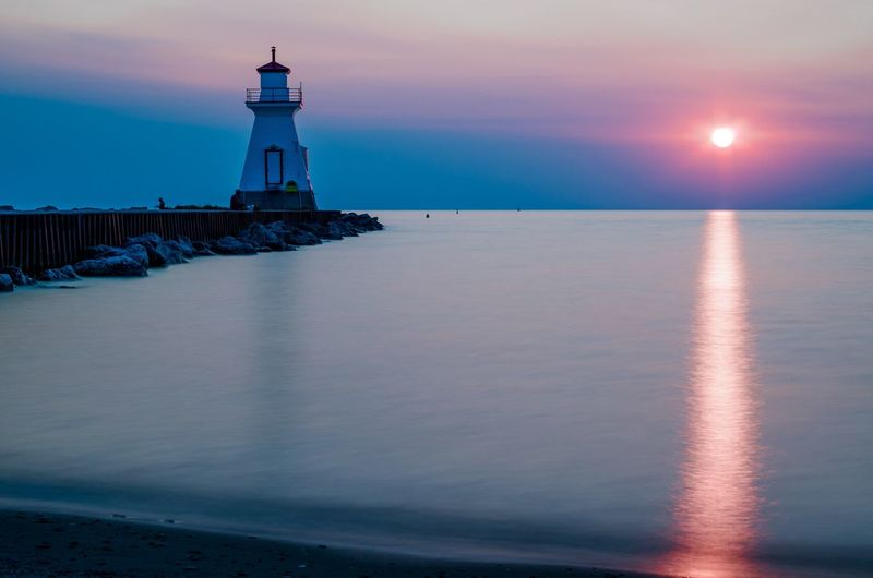 Lighthouse by lake huron against sunset sky