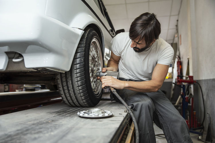 tires Mechanic Motor Vehicle Car Repairing Working Work Tool Adult Tire Men Wheel Garage Vehicle Breakdown Casual Clothing Auto Repair Shop One Person Occupation