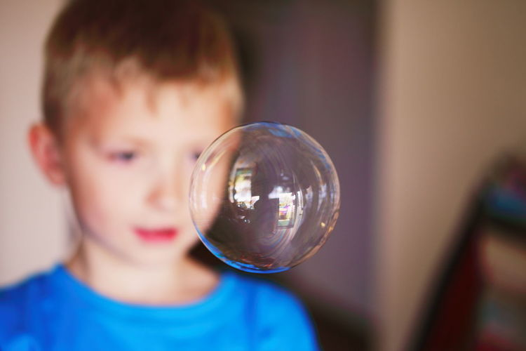 Close-Up Of Bubble Against Boy At Home