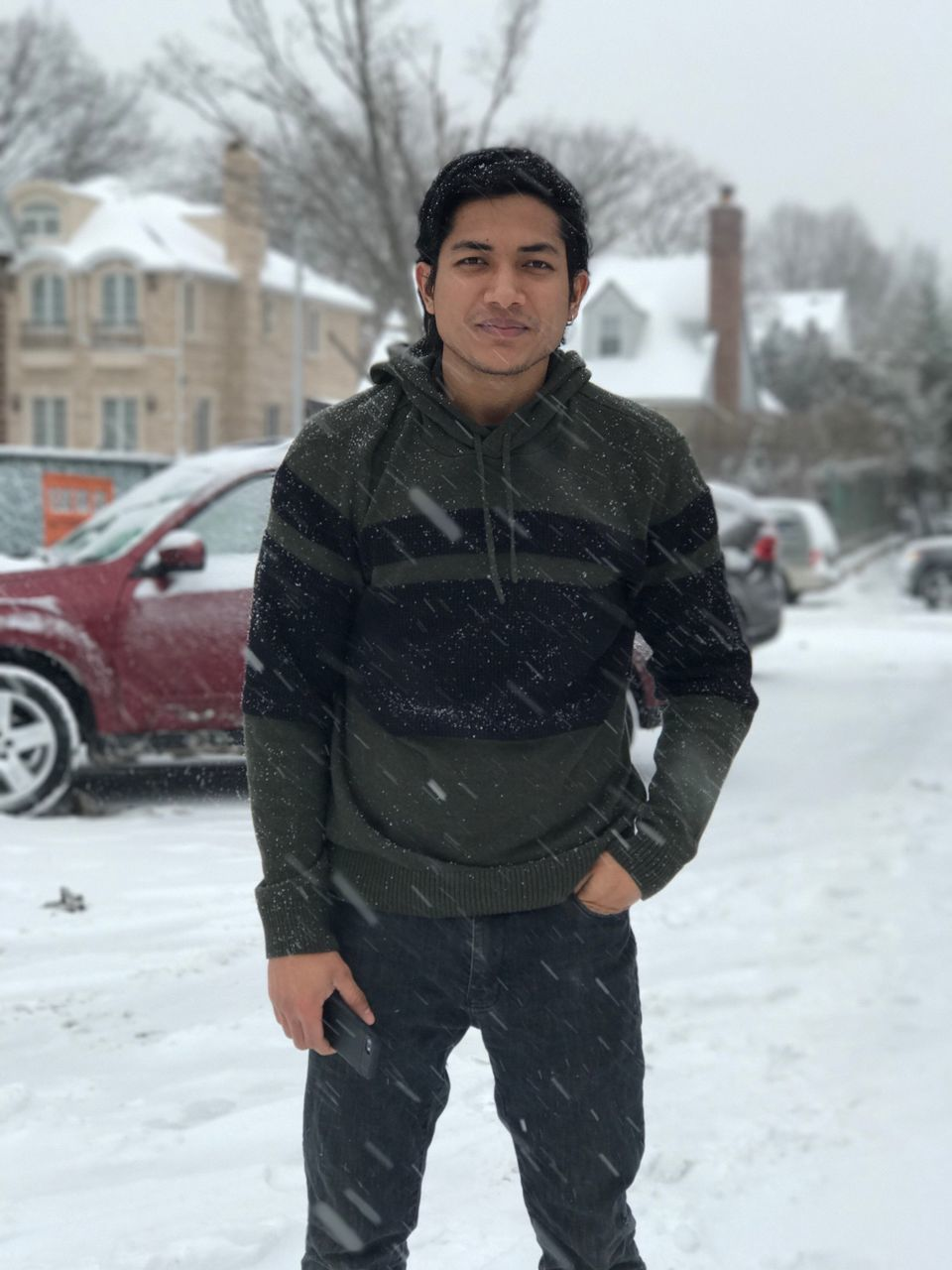 Portrait Of Young Man Standing Against Car On Snow Covered Road