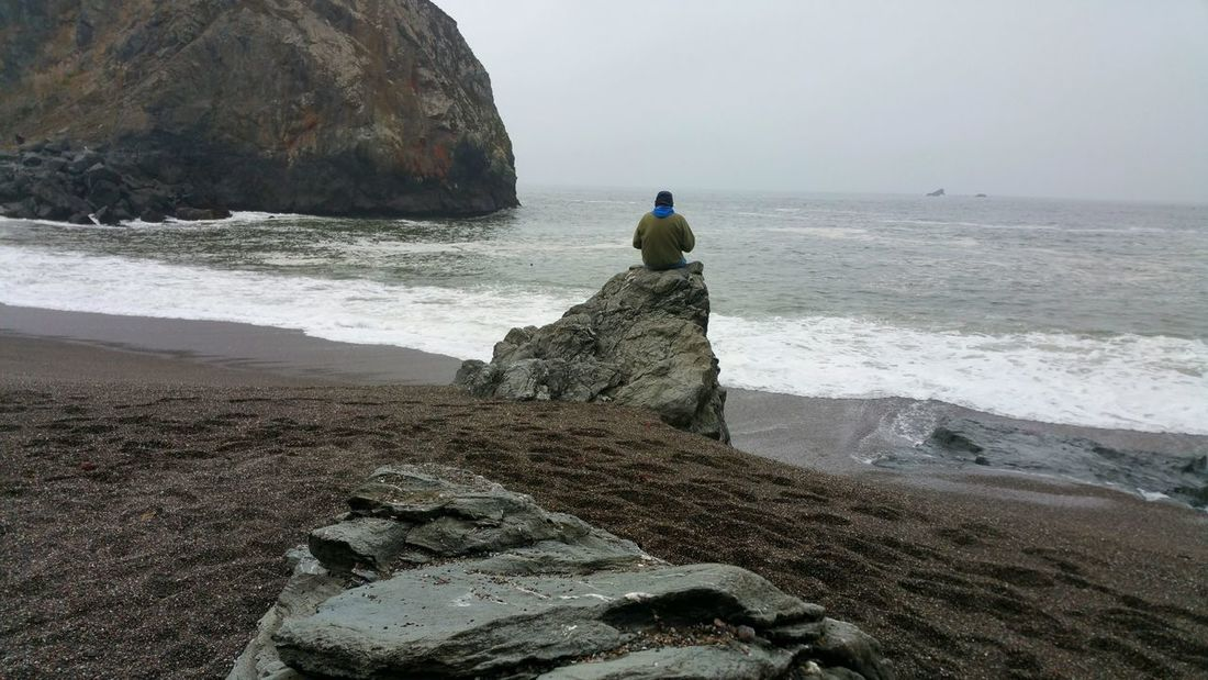 Just sitting on a boulder watching the world go by. Contemplating the wonders of the ocean. Man Hoody Blue Sitting Contemplating Watching Absorbing Restful Peaceful Calm Solitary Solitude Zen Foggy Clouds Atmospheric Moody Dramatic Mysterious Romantic Misty Water Sea Beach Wave Sand Fisherman Fishing Net Sky Horizon Over Water