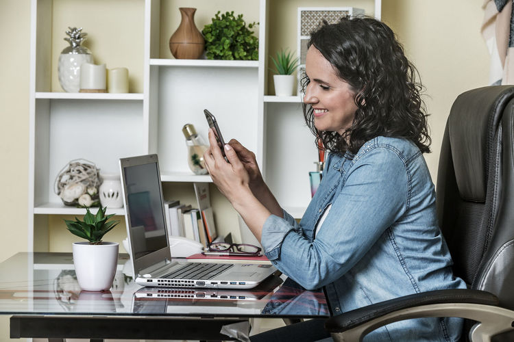 Side view of woman using phone while sitting on table