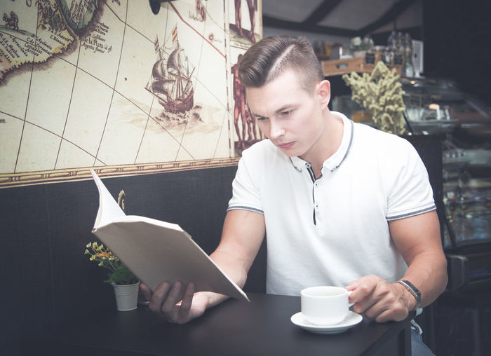 Young Man Reading Book While Having Drink In Cafe