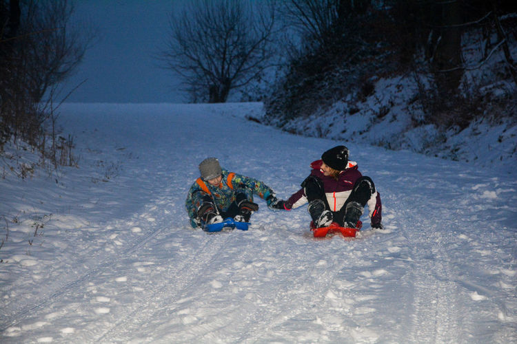 Boy and girl sitting in sled on snow