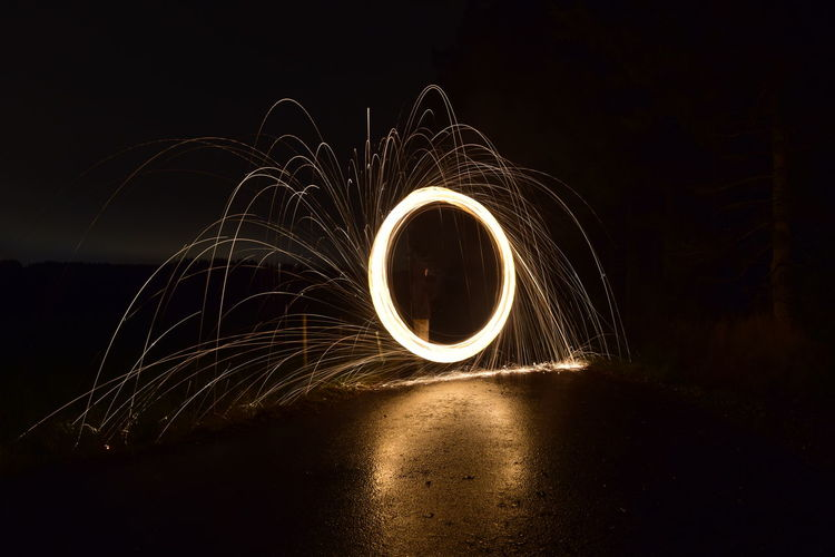 Person spinning wire wool against sky at night