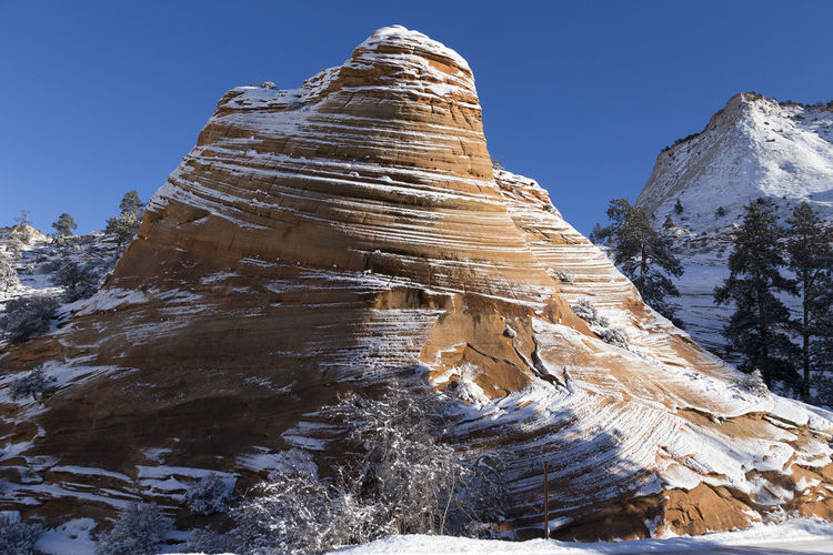 Beautiful wavy red rock formation under a light dusting of snow in Zion National Park, Utah, USA Beauty In Nature Scenics - Nature Nature Mountain Winter Rock Formation Clear Sky Rock Snow Low Angle View Zion National Park Wavy Dusting Of Snow Utah Southwestern Usa Early Morning Striations Formation Outdoors Cold Temperature Tranquility