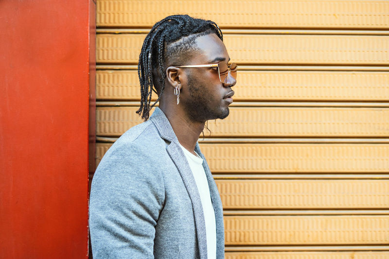 Side view of fashionable young man looking away by wall