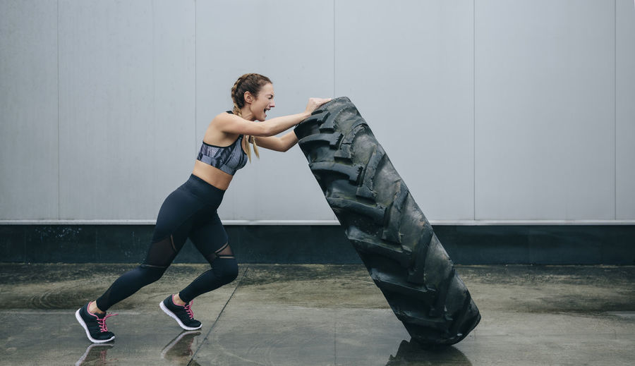 Full length of woman exercising with tire