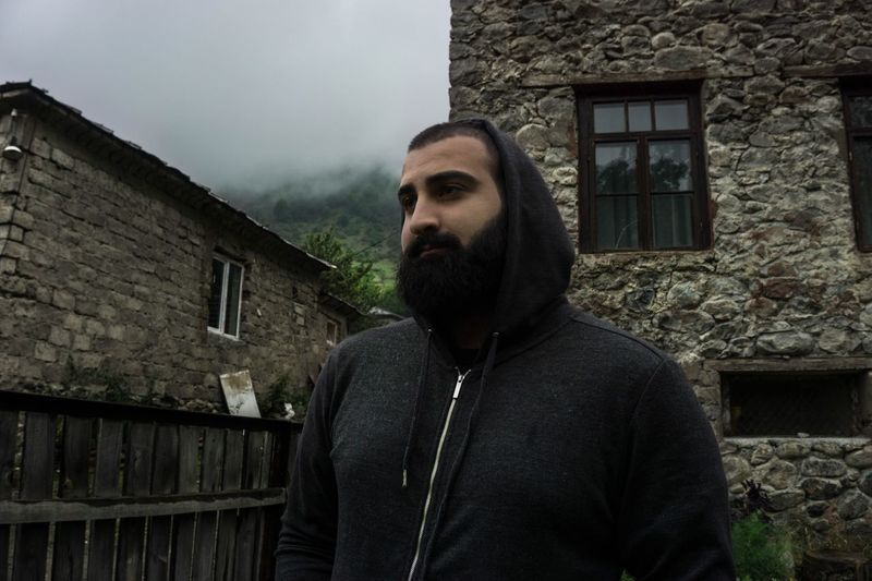 Thoughtful Bearded Man In Hooded Shirt Looking Away While Standing By Building