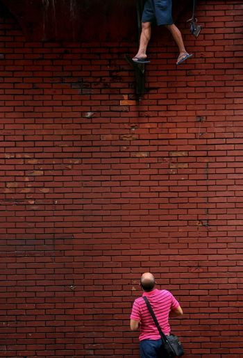 Rear View Of Man Looking At Person Standing Against Wall