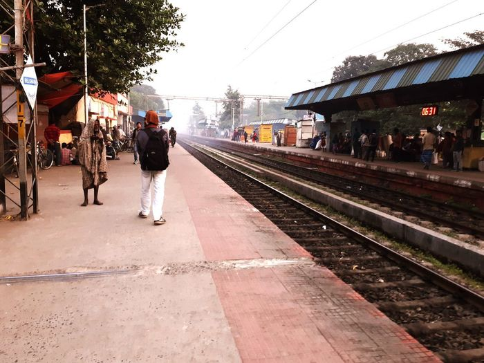 People waiting at railroad station in city against sky