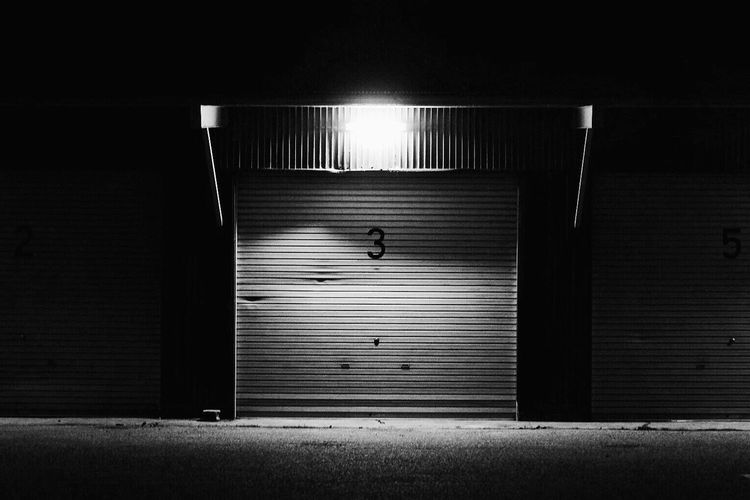 Number 3 on closed shutter of store at night