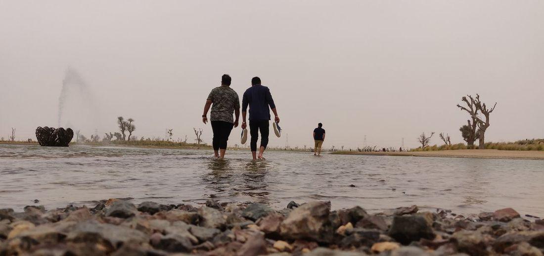 LOVE LAKE, QUDRA Explore Water Togetherness Men Beach Walking Sky Low Tide Mud