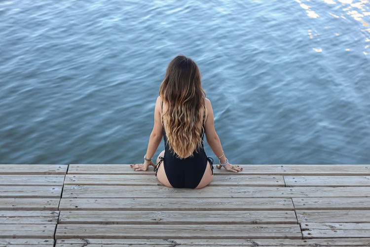 Rear view of woman wearing swimwear sitting on plank by river