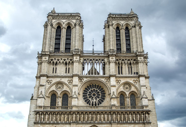 From below ornamental facade of old Notre-Dame Cathedral on cloudy sky background In Paris, France France Notre Dame De Paris Notre-Dame Paris Travel Architecture Building Building Exterior Cloud - Sky Day Destination History Landmark Low Angle View No People Outdoors Place Of Worship Religion Sky Spirituality The Past Tower Travel Destinations