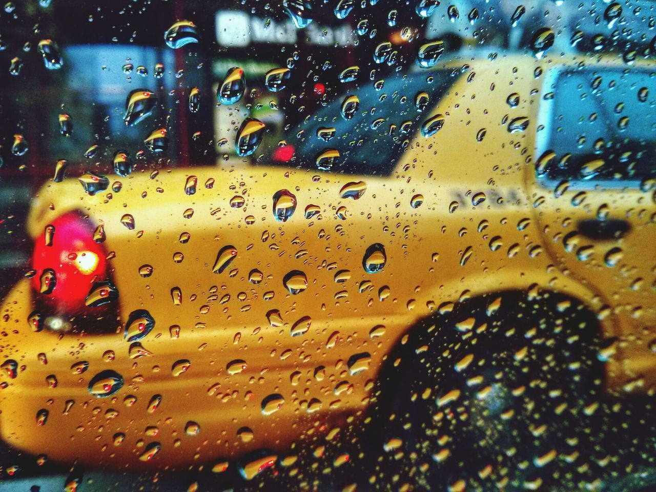 View of yellow car across wet glass