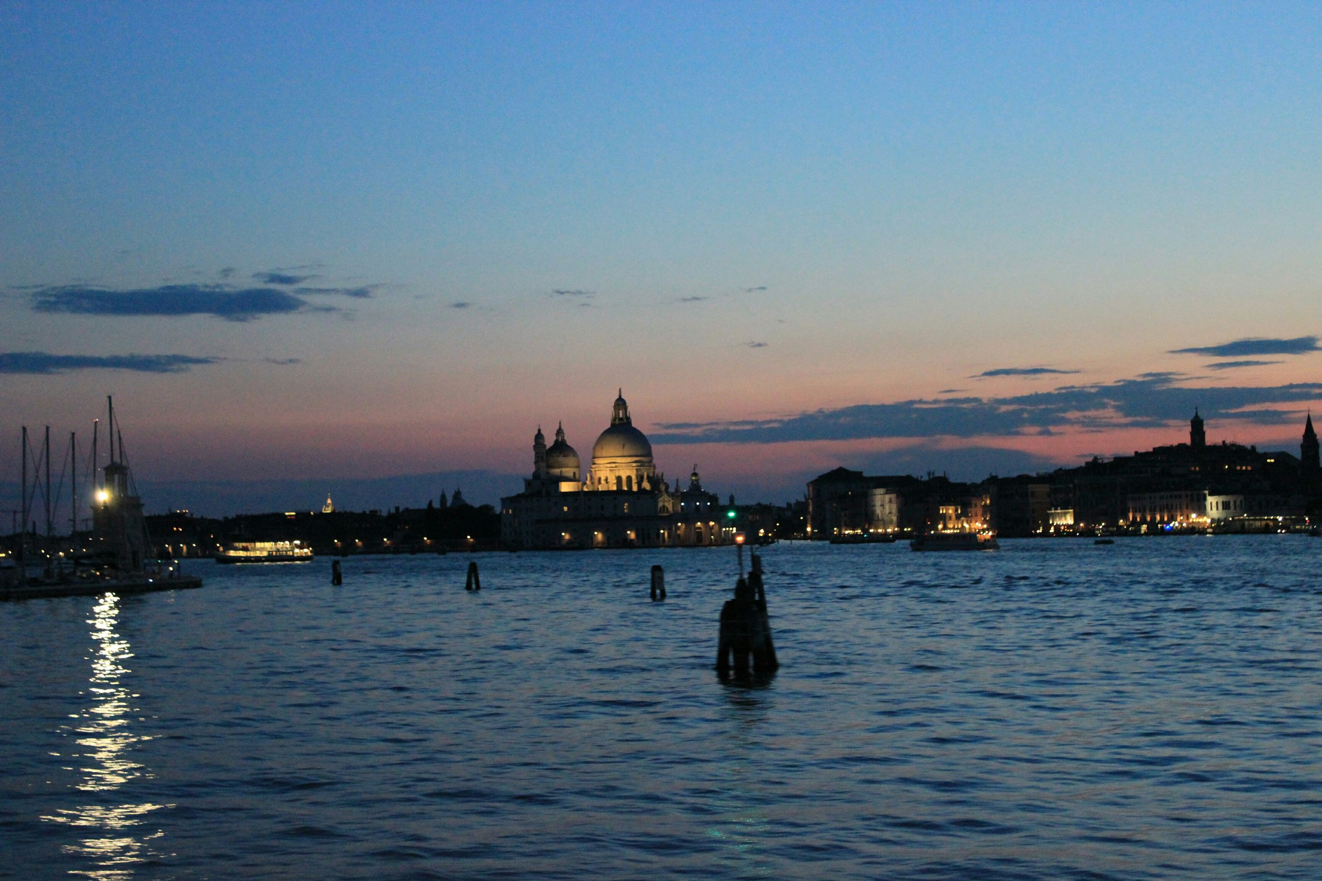 water, illuminated, waterfront, building exterior, sea, sky, architecture, built structure, dusk, sunset, night, silhouette, scenics, copy space, tranquility, reflection, city, tranquil scene, river, rippled
