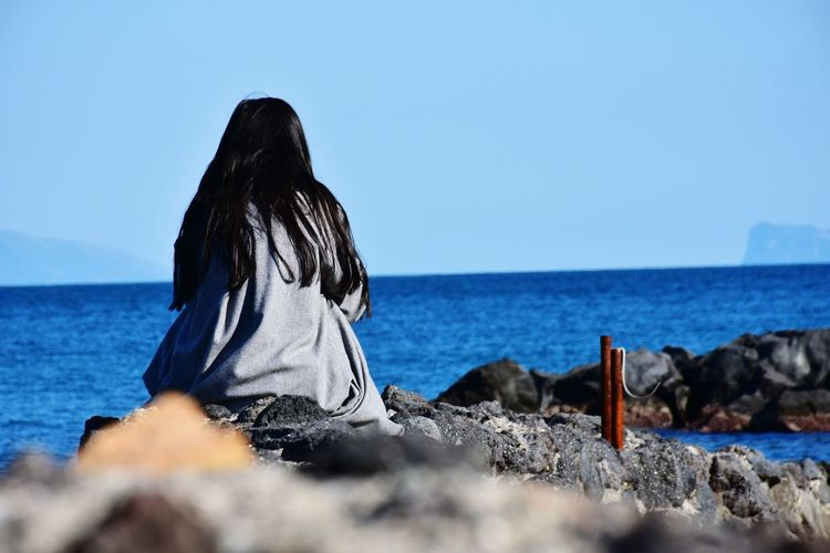 Rear View Of Woman Sitting On Rocks At Sea Shore Against Clear Sky