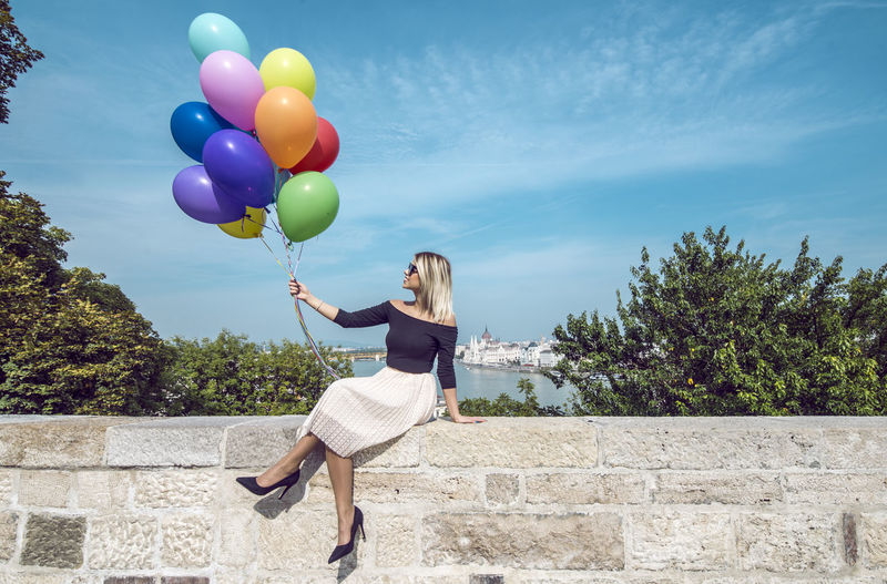 Woman holding balloons while sitting on retaining wall against blue sky