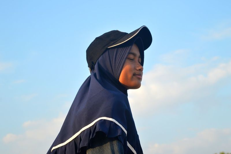 Low angle view of woman wearing cap standing against sky