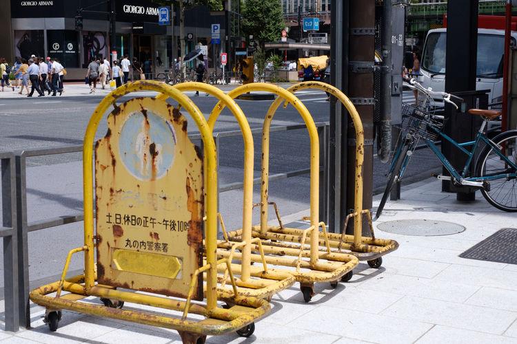 Information sign on sidewalk by street in city