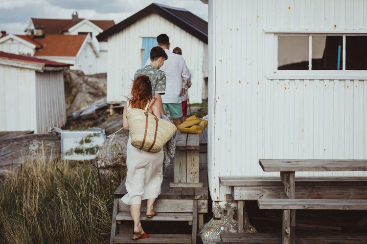 Rear view of couple standing outside house