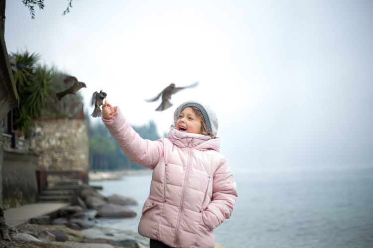 Girl feeding birds while standing by sea against sky