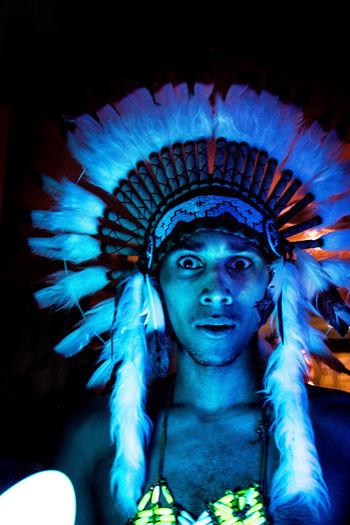 Portrait of man wearing headdress in darkroom