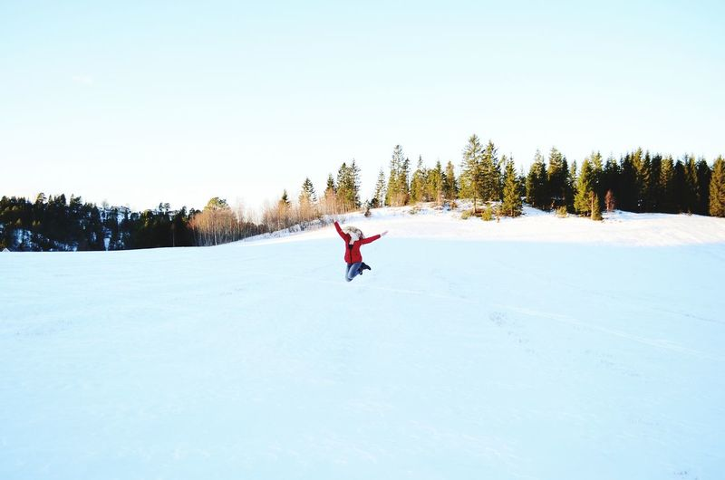 Excited woman jumping on snow against sky