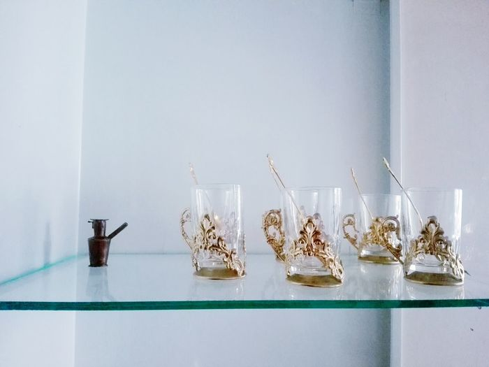 Drinking Glasses On Glass Shelf Against Wall At Home