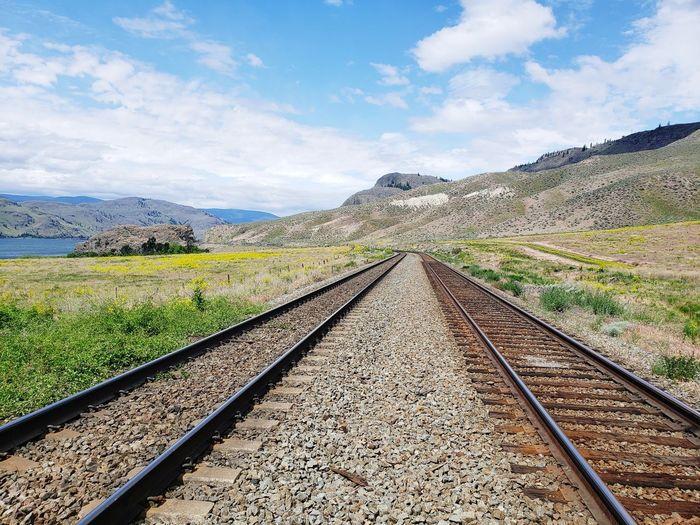 Railroad tracks leading towards mountain against sky