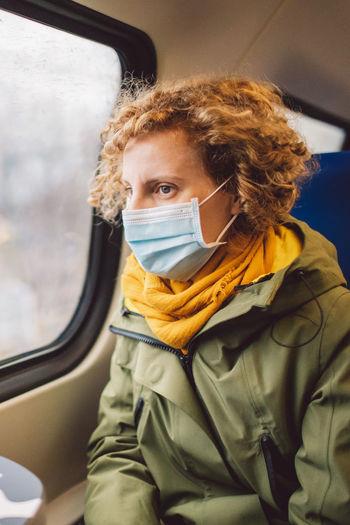 Woman wearing mask sitting in car