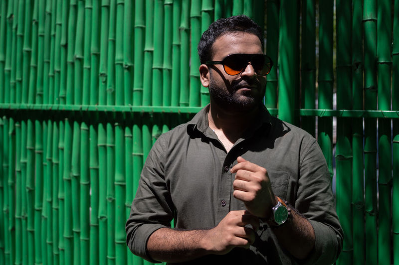 Man in sunglasses standing against wall during sunny day