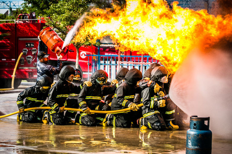 Firefighter spraying water on fire