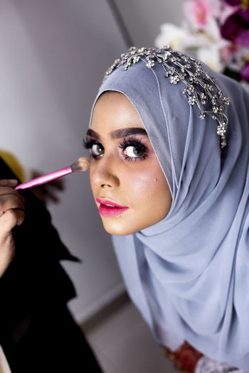 Cropped Hand Applying Make-Up On Woman Wearing Hijab