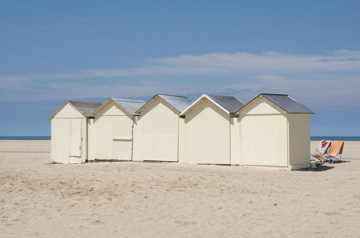 Beach huts on sandy beach Architecture Beach Beach Huts Blue Sky And Clouds Built Structure Day Deck Chairs Nature No People Outdoors Ouïstreham Sand Sandy Beach Sea Sky Summer Tranquility Vacations