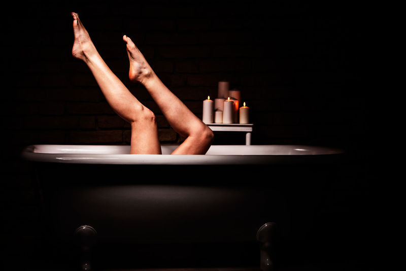 Low Section Of Young Woman In Bathtub Against Black Background