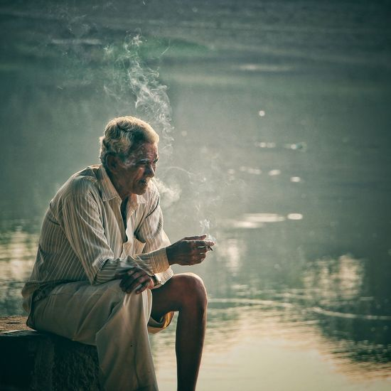 Thoughtful senior man smoking by lake