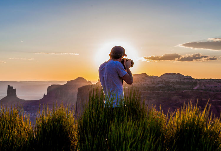 Rear view of man photographing during sunset