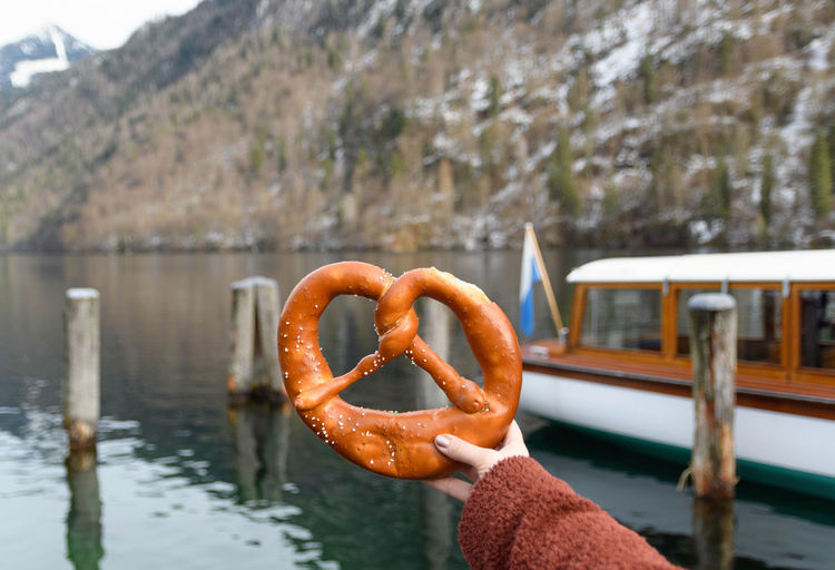Woman holding a pretzel.
