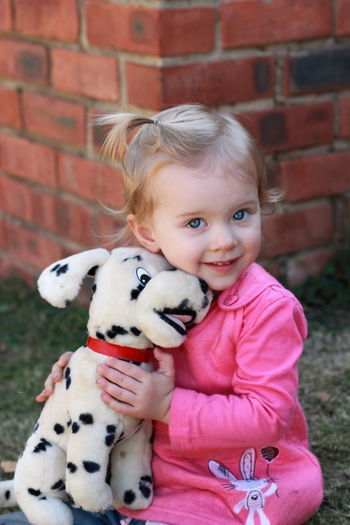 Portrait Of Cute Girl With Stuffed Toy Sitting In Yard Against Brick Wall