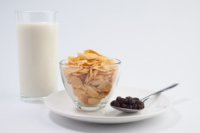 Close-up of breakfast cereals in bowl and milk against white background