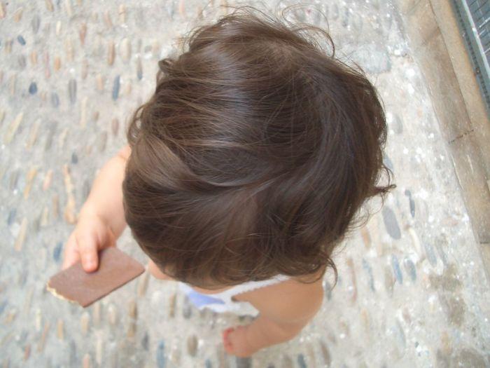 High angle view of girl holding chocolate bar on walkway
