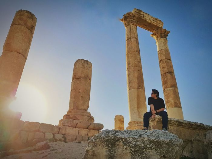Woman sitting on old ruin against sky