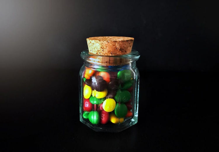Close-up of multi colored candies in jar against black background
