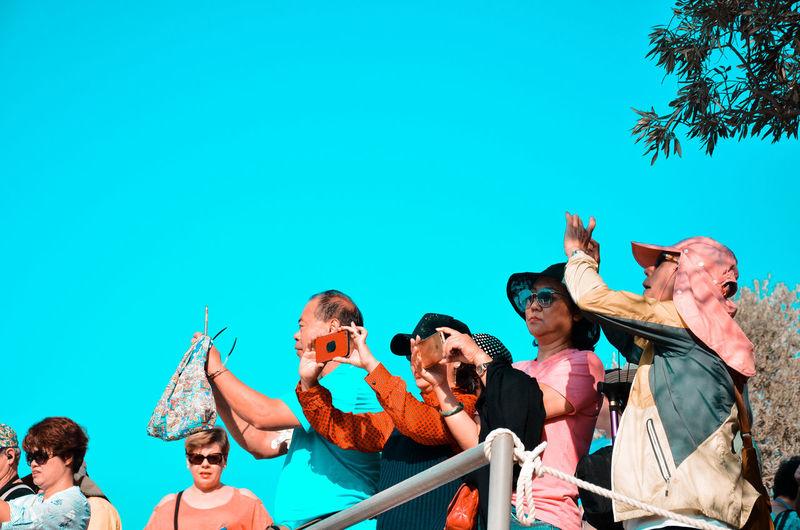 People standing against blue sky